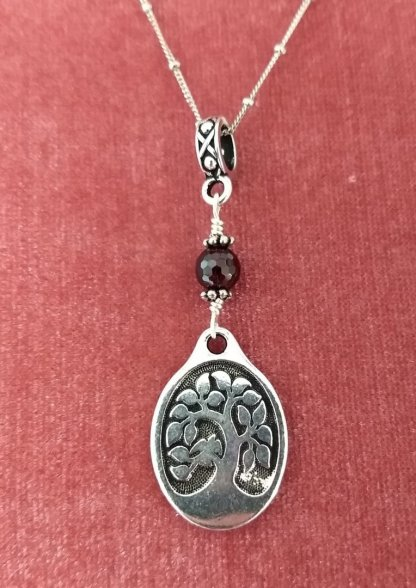 oval tree of Life with faceted Garnet accent